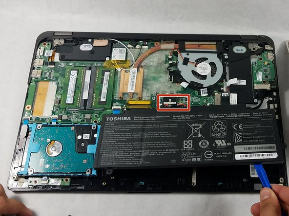 Use a plastic opening tool to lift the side of the battery that is closest to the long edge of the computer.