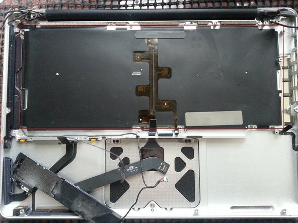 Carefully peel the black keyboard backlight from the upper case.