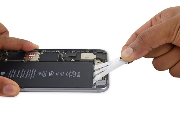 Gently pull the battery adhesive tabs away from the battery, toward the bottom of the iPhone.