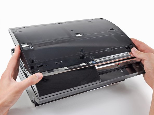 Lift the top cover from its rear edge and rotate it toward the front of the PS3.