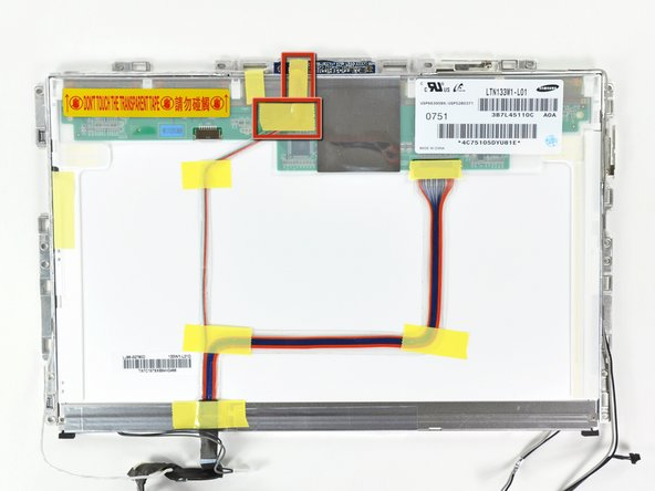 Remove the two pieces of yellow tape covering the camera cable near the top edge of the LCD assembly.