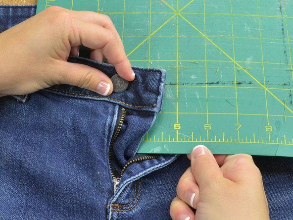 Place a flat work surface like a scrap piece of wood or a cutting board directly beneath the tack and between the front and back of the jeans.