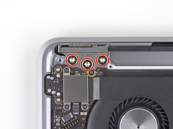 Use a T9 Torx driver to remove the six 4.9 mm screws securing the display hinges to the upper case.
