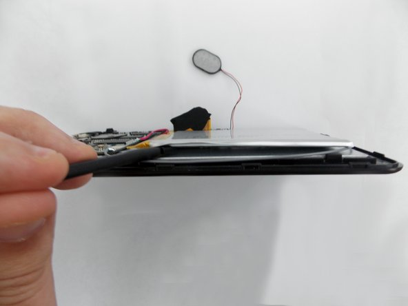 Insert the flat end of the spudger tool  in the crack beneath the battery.