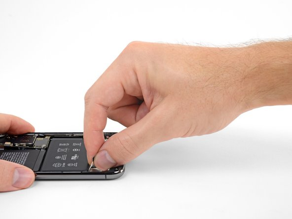Grab one of the outer battery adhesive tabs and slowly pull it away from the battery, toward the bottom of the iPhone.