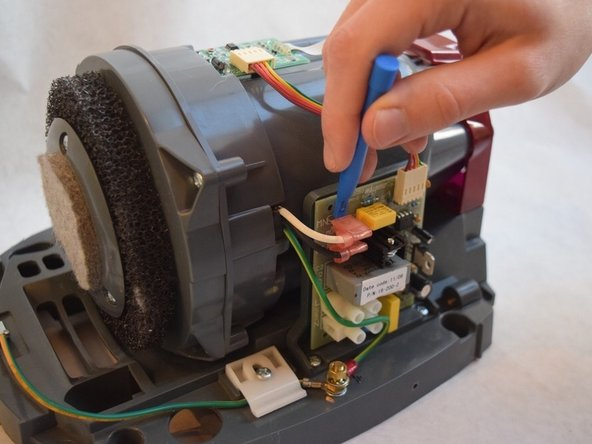 Use a plastic opening tool to remove the two pink capped wires in the upper left corner of the server board.