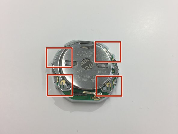 Remove the Battery Holder surrounding the circuitry of the watch by carefully pulling off each of the four clips.
