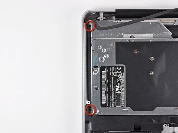Remove the two 3.5 mm Phillips screws securing the outer side of the optical drive to the upper case.