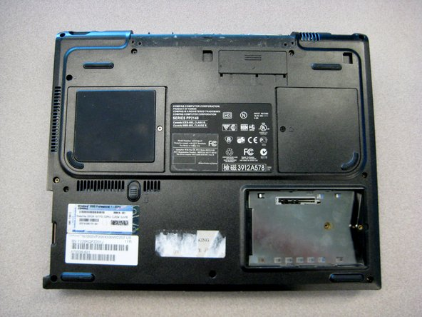Turn the laptop bottom side up with the rear panel facing forward.