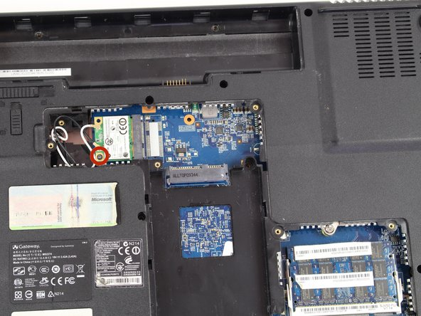 """Remove the 3/16"""" Phillips #0 screw located at the bottom left corner of the WiFi card."""