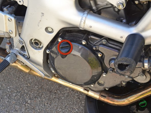 Locate the oil filler cap on top of the clutch cover.