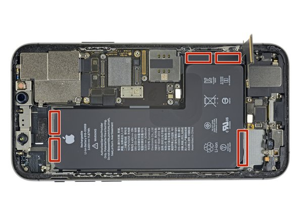 The battery is secured to the rear case with three pieces of stretch-release adhesive—one near the bottom edge of the battery, one near the top, and one on the right.