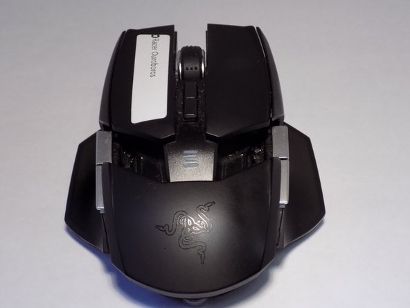 Use a Phillips #00 screwdriver to loosen the two captive screws from the bottom of the mouse.