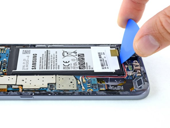 Use an opening pick to pry up the battery from the bottom.
