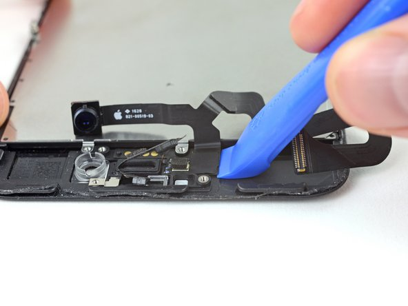 Insert the sharp edge of an iFixit opening tool underneath the camera assembly's flex cable, on the opposite side from the front-facing camera.