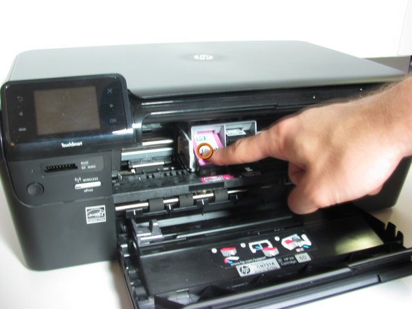 Press down on the head of the ink cartridge that needs replacing.  This will release the cartridge and allow you to pull it out.
