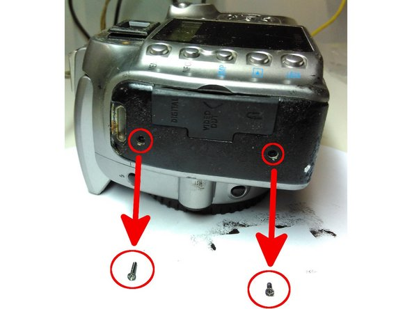"""Remove the black screws from the camera's left rubber covering - note it is a 5/16"""" screw at the top and a 3/16"""" screw at the bottom."""