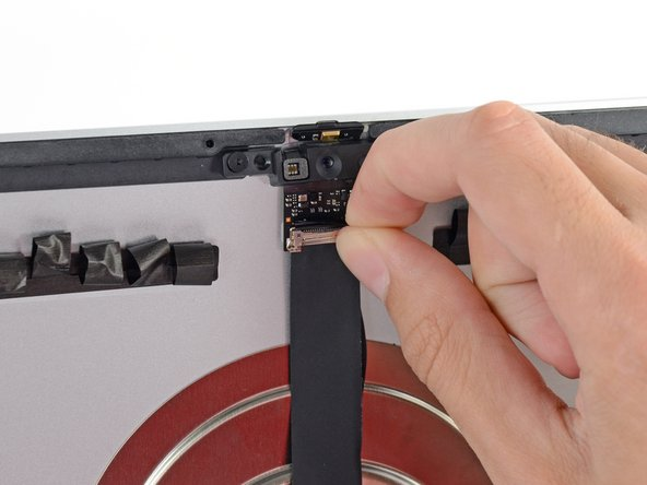 Flip down the metal retaining bracket on the iSight camera cable.