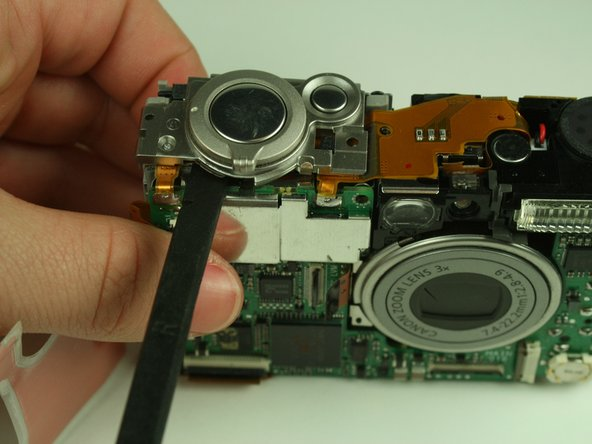 Using a spudger, gently detach the shutter button assembly from the camera.