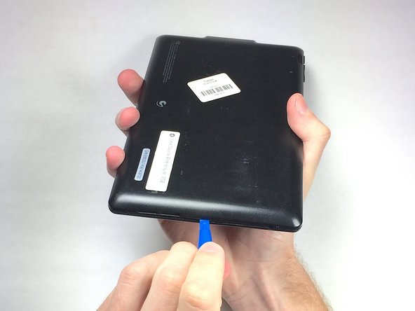 Insert the plastic opening tool into the middle of the bottom edge of the device. The tool should be inserted within the seam between the back and front covers.