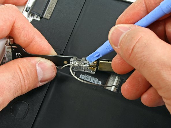 Using an iPod opening tool, carefully remove the plastic cover shielding the WiFi/Bluetooth board and dock connector cable.