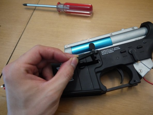 Reinstall the mag catch, then place the spring on the post and the button on top of it. Tighten the screw that holds the button in place.