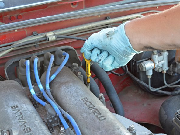 Open the hood again and locate the yellow oil dipstick at the rear of the engine on the right side.