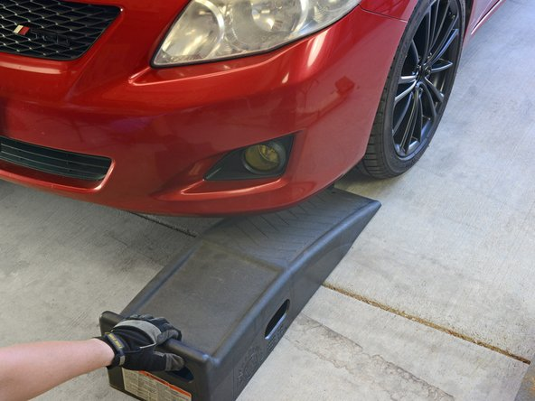 Slide the first ramp directly in front of the vehicle's front, driver-side wheel, until it touches the rubber of the tire.
