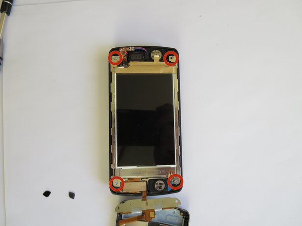 Remove the four 1.5mm #000 Phillips screws at each of the corners of the phone, using the Phillips #000 screwdriver.