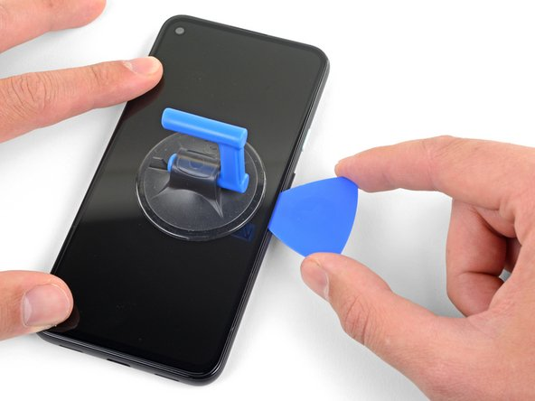 Slide the pick along the right edge of the screen to cut the adhesive.