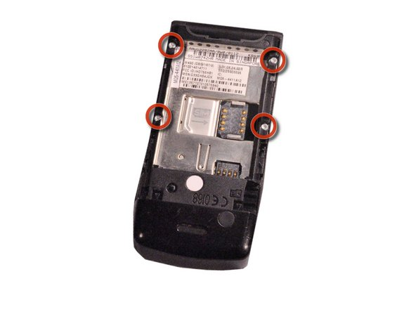 After taking out the battery, locate four star-shaped 5.4 mm T6 screws on top and middle of the rear of the phone. Indicated by the red circles.