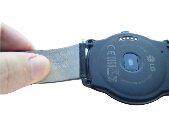 Once the spring bar is released, pull out the other end to detach the strap.