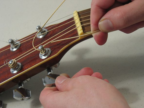 Wind the string until it is somewhat tight, and then press it into the fretboard channel.
