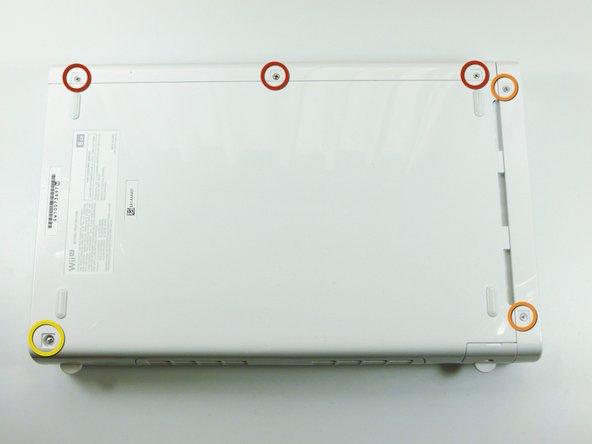コンソールの底面を上向きにして、白い正方形のステッカーの下に隠された6本のネジを外します。