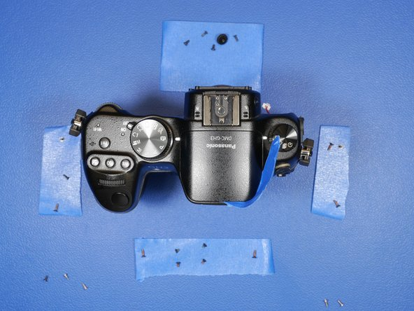 Take this doubled over piece of tape and forcefully shove it toward the back of the flash camera unit. This will trigger the pop-up flash latch release inside the camera and allow you to continue the disassembly without ever needing power!