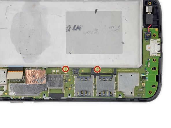 Use a T3 Torx driver to remove the two bronze-colored, 2.4 mm screws securing the motherboard.