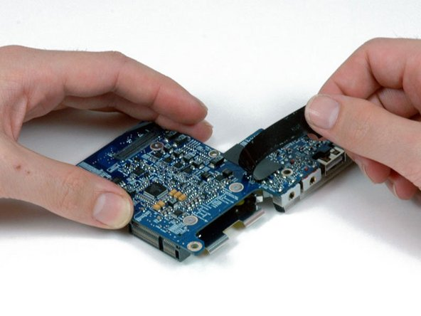 Peel up the L-shaped piece of black tape on the I/O board to reveal the two silver Phillips screws beneath.