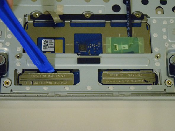 Use a plastic opening tool to disconnect the metal trackpad support brackets.