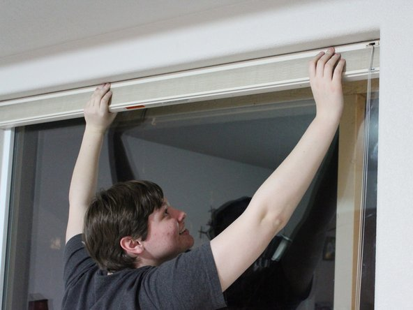 Rehang the shade by pushing the shade up into the clips and sliding it towards the window.