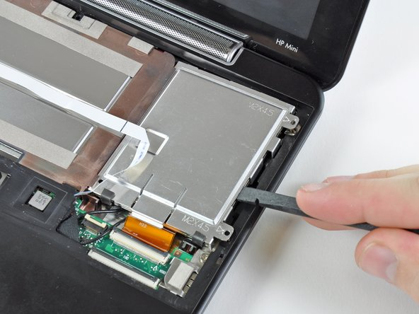 Lift the hard drive up and out of the lower case, being careful not to damage its cable in the process.