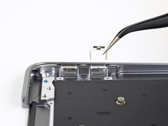 Lift the USB-C port brackets out of their recesses in the upper case and remove them.