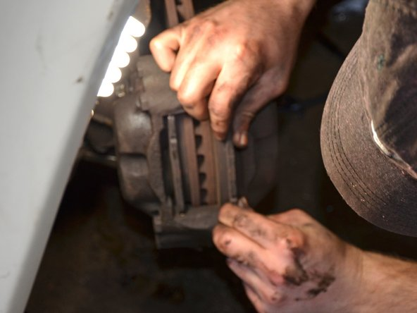 Using your hands or a screwdriver, lift the inner and outer brake pads out of the brake caliper.