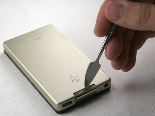 Use a metal spudger or Zune opening tool to remove the small silver plastic cap on top of the device.