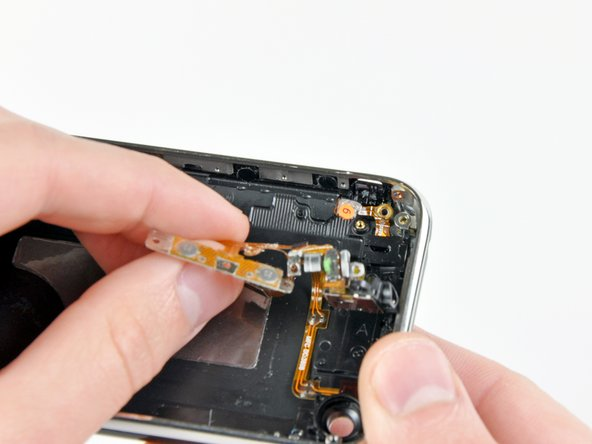Gently pull the headphone jack electronics away from the side of the rear panel to reveal the plastic mute switch.