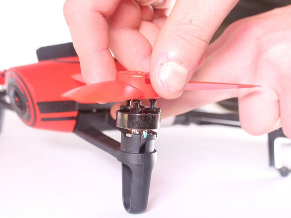 While gently pushing down on the arm of which the propeller is attached, pull the propeller up off the motor.