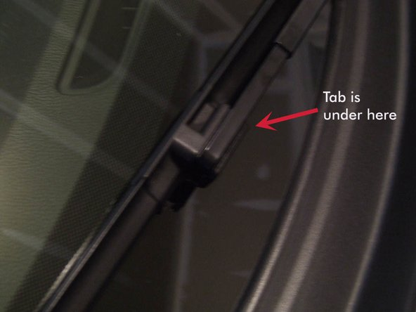 """The first thing the manual tells you is to lift both arms, and remove the wipers. Like a lot of wipers, this is """"locked"""" onto the arm by sliding the wiper assembly from the base of the arm into a crooked end, where it snaps in place. Depress the spring tab towards the wiper arm, and gently slide the wiper down towards the base of the wiper arm."""