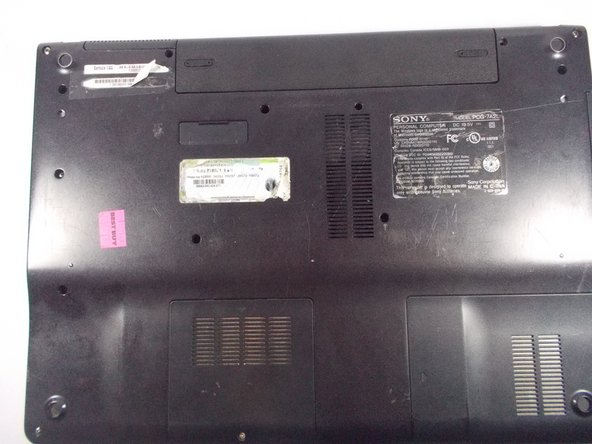 """Flip laptop over so that """"Service TAG"""" is at the top left."""