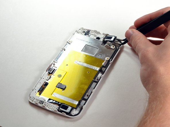 With the motherboard off, use tweezers to grab the top speaker.
