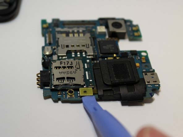 Using the plastic opening tool, detach the tab connecting the speaker to the motherboard.