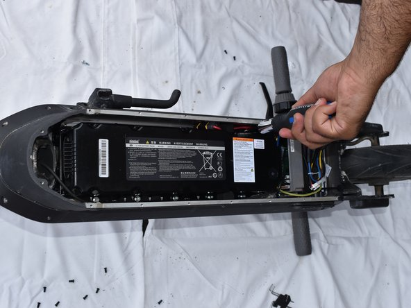 Unscrew the 10 screws that hold the battery onto the frame and remove the battery from the enclosure.